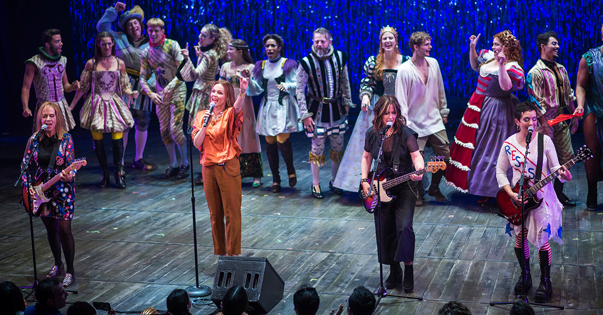 Go-Go's band members onstage with instruments and members of 'Head Over Heels' in costume behind them