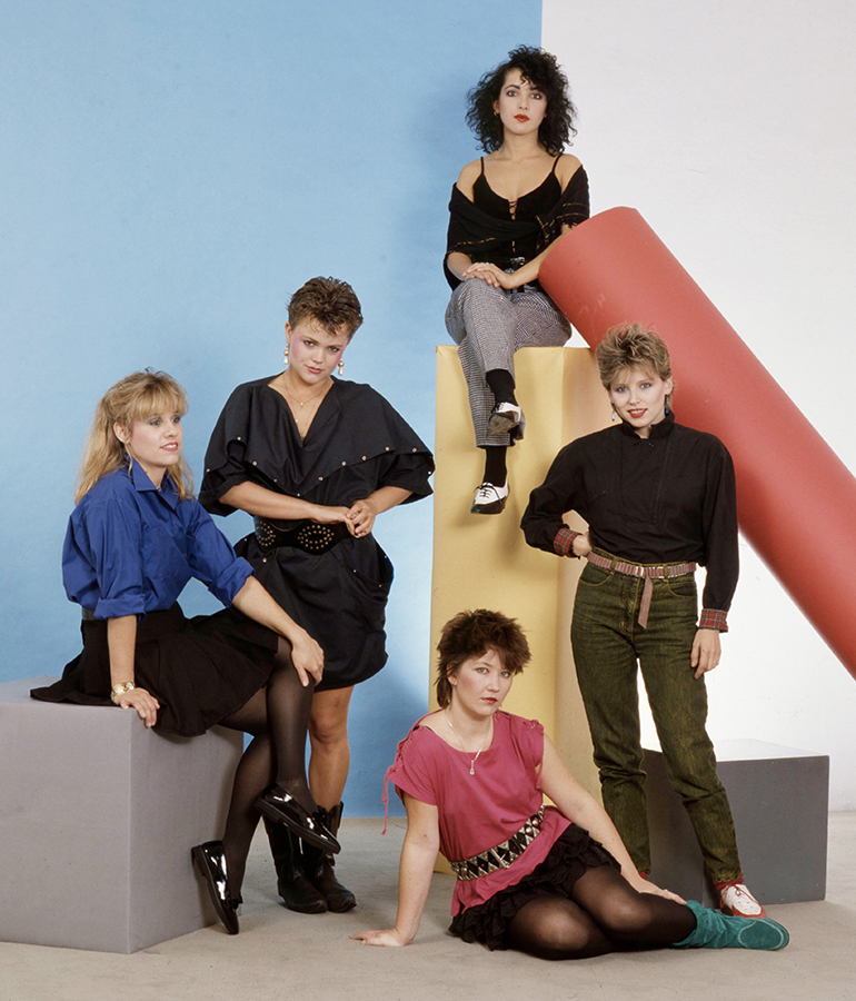 1982 studio portrait of the Go-Go's sitting and standing on and near large colorful blocks