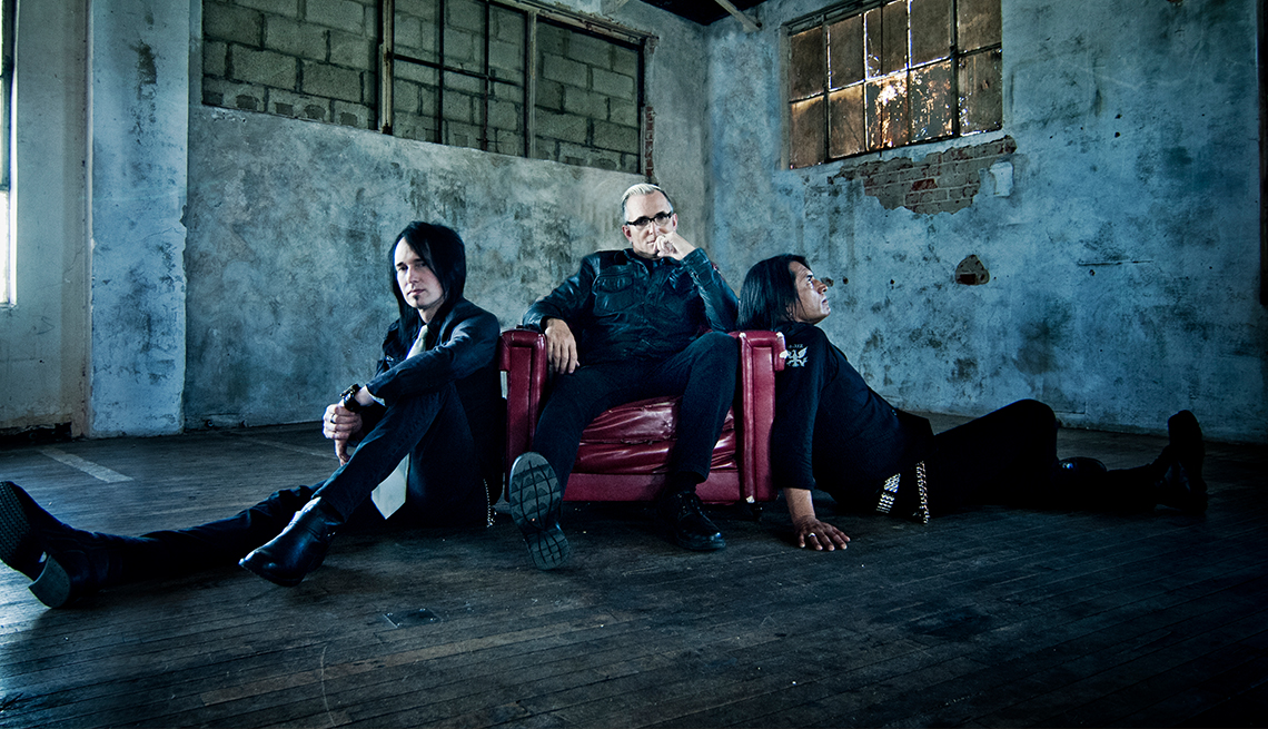Art Alexakis sitting on a burgundy leather chair with Davey French and Freddy Herrera leaning against it in a room with cement and cinderblock walls