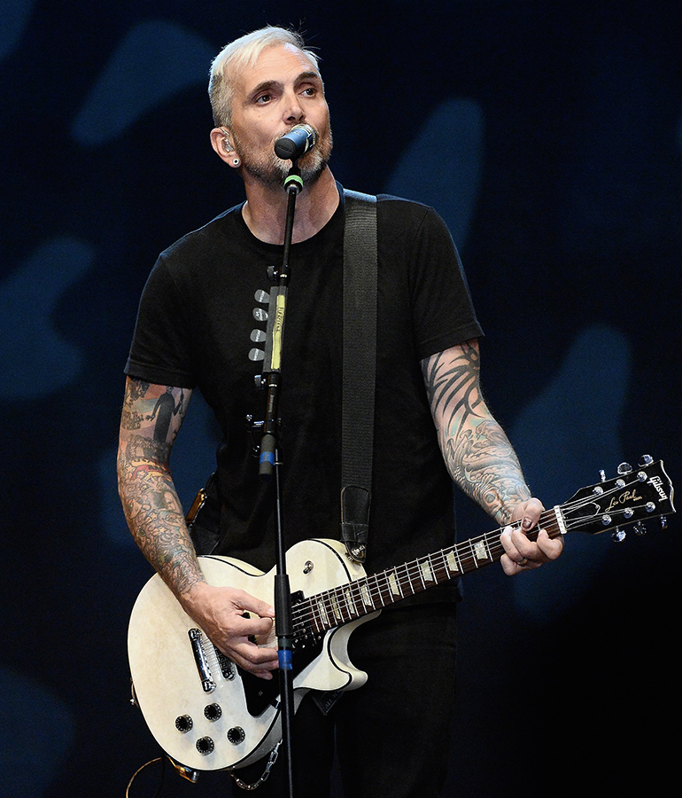 Everclear's Art Alexakis with tattoo-covered arms singing into microphone and playing guitar