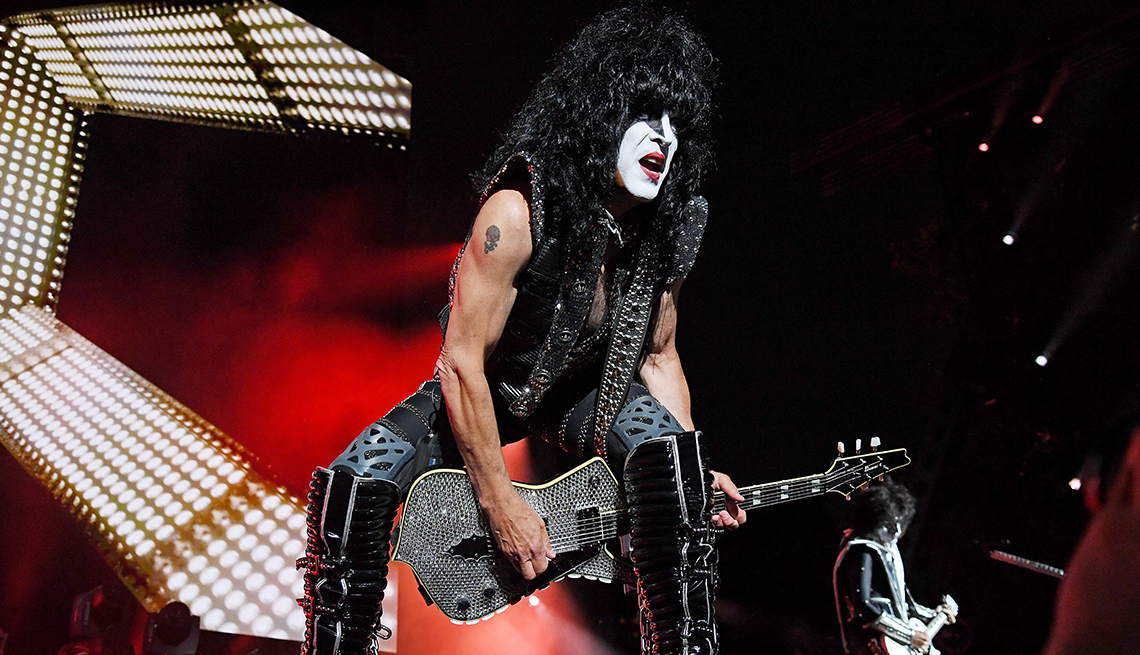 Paul Stanley playing guitar onstage wearing boots, white face paint, black pants and tank top