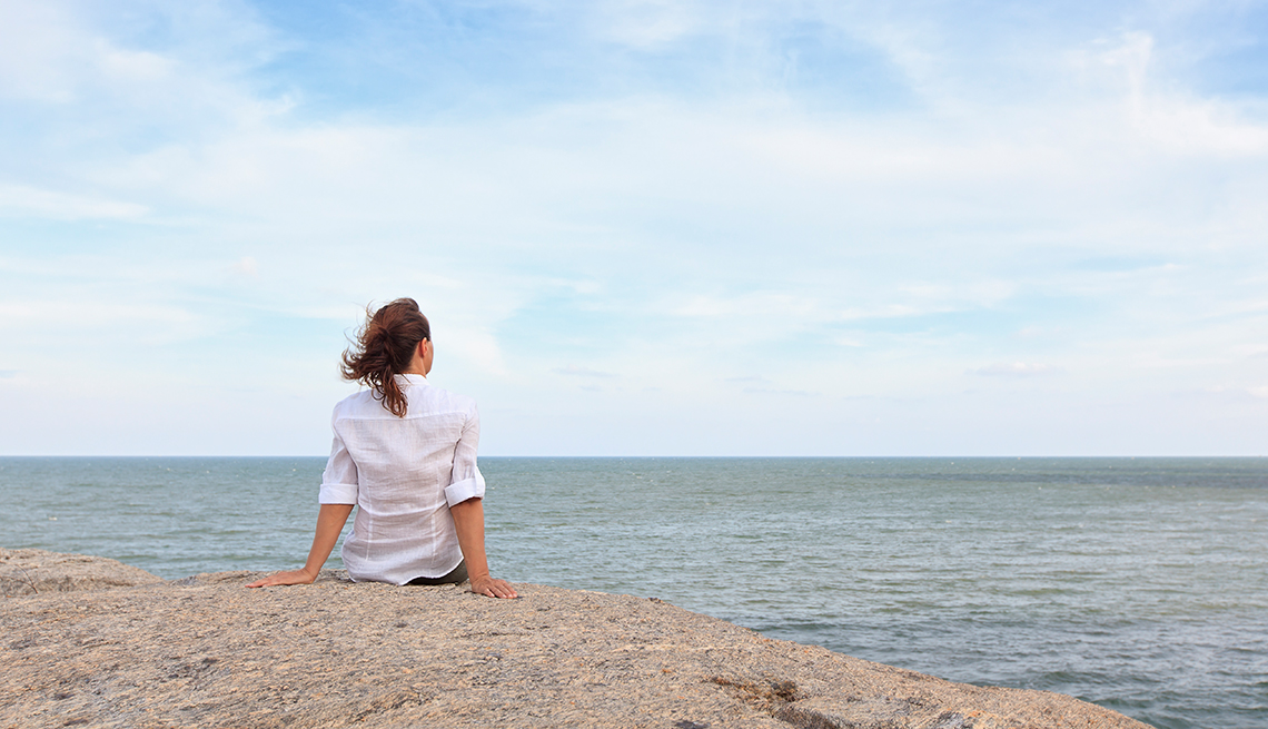 woman sitting on a rock looking out over the ocean