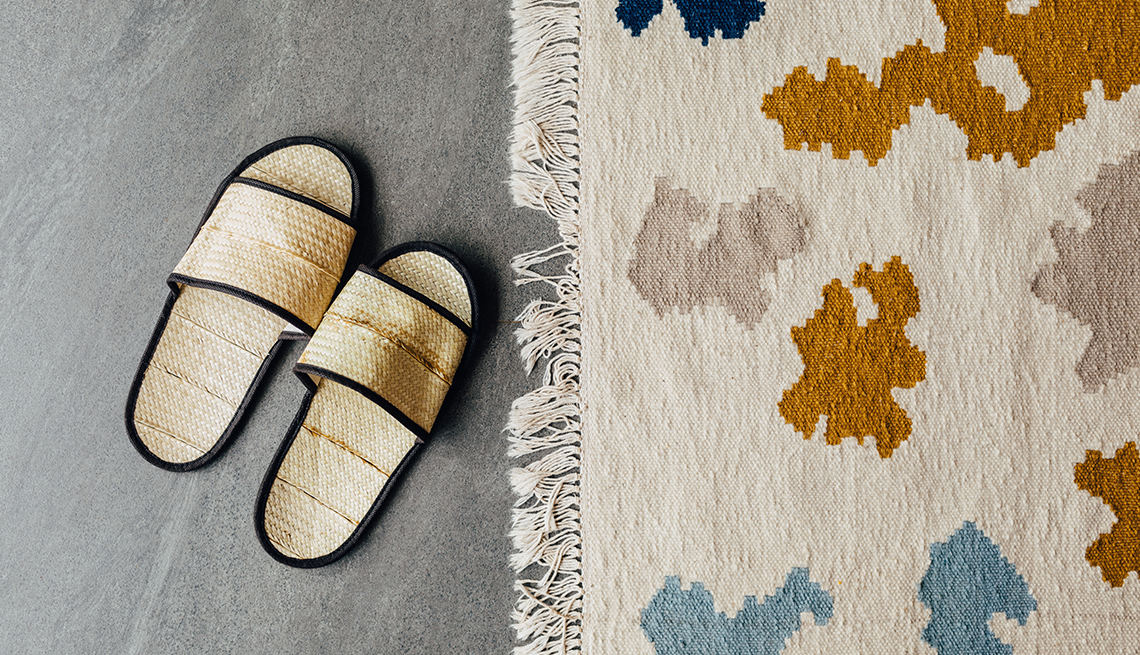 pair of slippers next to an area rug