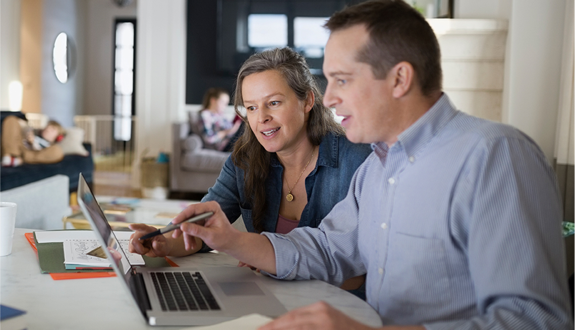 Man and woman working at a table looking at a laptop computer