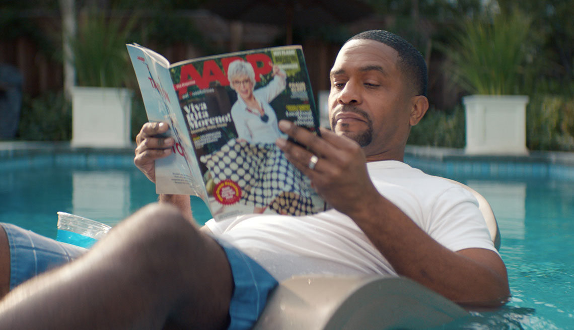 Man floating on a raft in a swimming pool reading an A A R P magazine