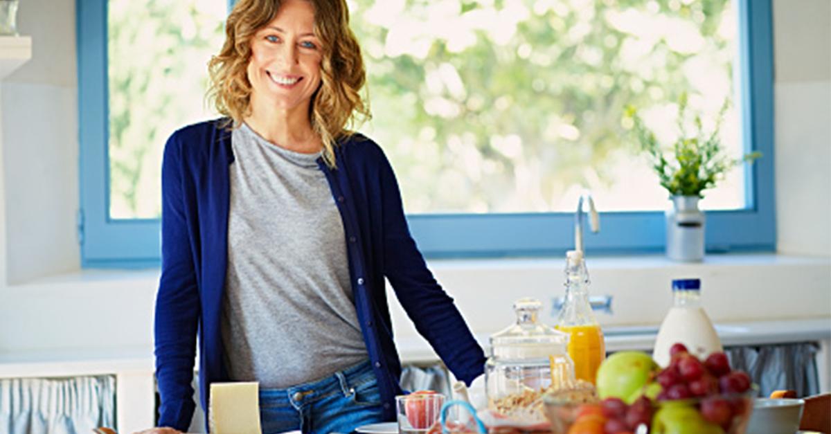mujer en una cocina frente a una serie de ingredientes