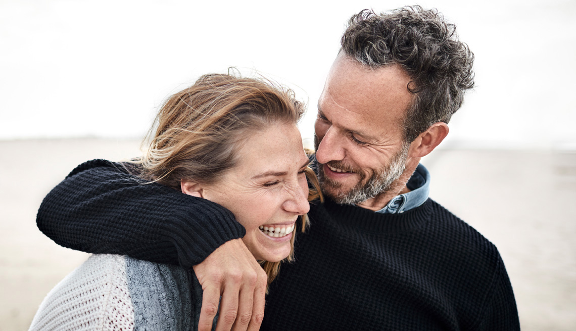 couple laughing together on a beach