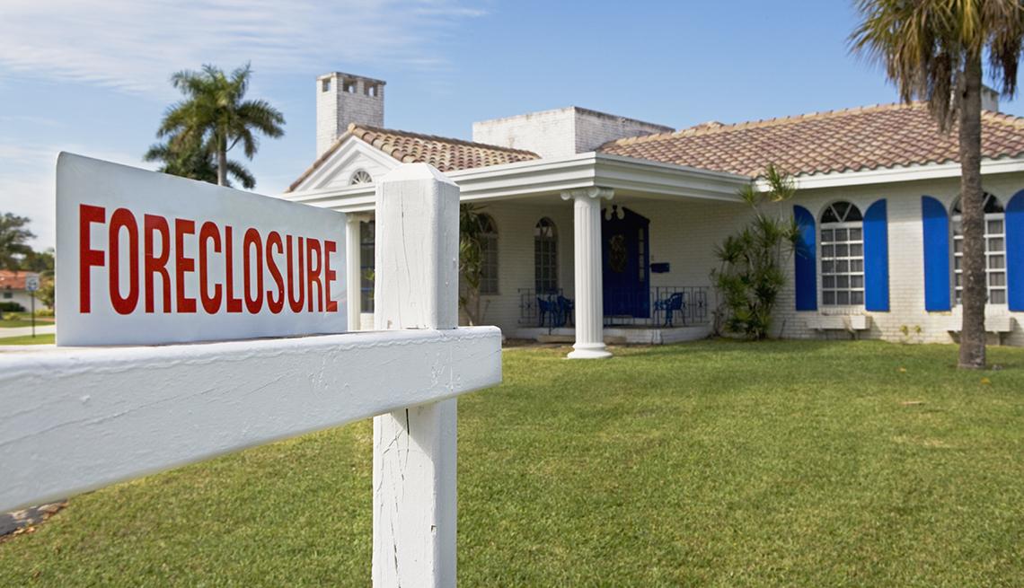 Letrero de juicio hipotecario frente a una casa