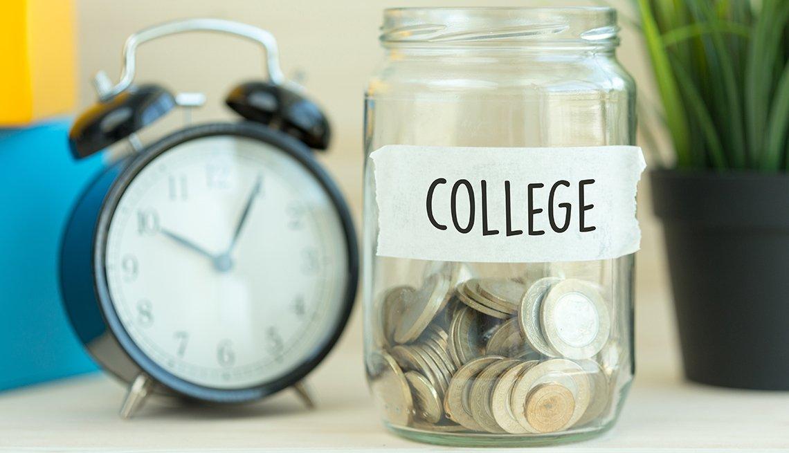 Reloj al lado de una jarra con monedas y un letrero que dice universidad en inglés