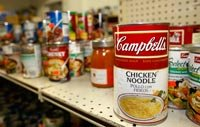 dented cans of soup and other canned goods sit on a store shelf