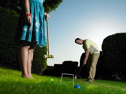 man and young woman playing croquet