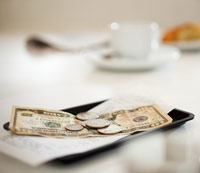 dollar bills and coins on tip tray