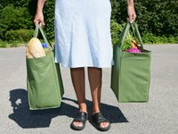 woman with a filled reusable grocery bag in each hand