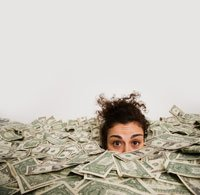 Studio shot of woman up to her eyes in money
