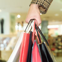 close-up of female shopper carrying numerous bags
