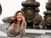 Mujer usando su celular en un puente en Paris - Uso del celular en paises extrangeros