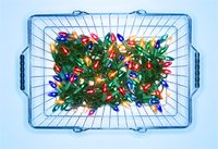 Illuminated Christmas lights in shopping basket on blue background
