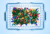 Illuminated Christmas lights in shopping basket on blue background