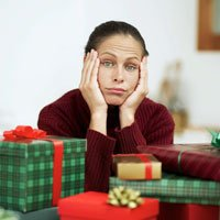 disillusiond woman at christmas with lots of wrapped gifts