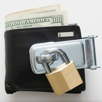 Americans are saving money rather than spending it- a wallet full of cash with a padlock on it