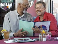Couple peruses menu - free restaurant coupons offer dining discounts and make good gifts
