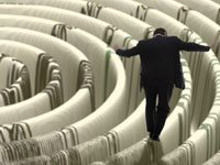 Man balancing money maze - 8 ways to avoid bank fees