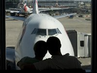 Couple looks out airport window - one needs to search for senior airfares and many are not online
