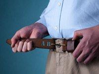 Hombre amarrándose un cinturón con las letras A y B como huecos