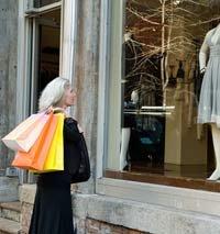 Mujer al frente de un almacen con unas bolsas de compras