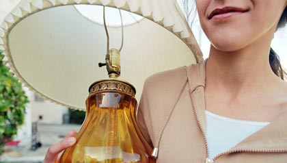 A woman holding a glass lamp at a yard sale.