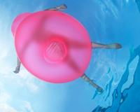Una persona flota en una piscina sobre una balsa rosada de plástico