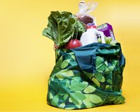 A reusable shopping bag full of groceries 99 ways to save money on shopping