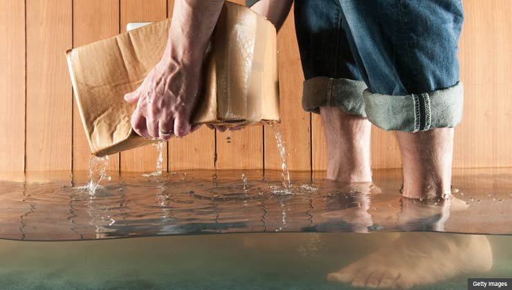Man in flooded basement picking up a soaked box of papers