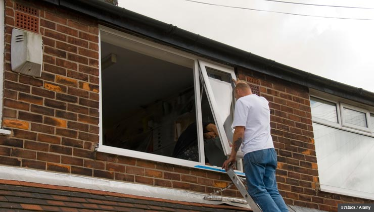 Man on ladder fixing windows