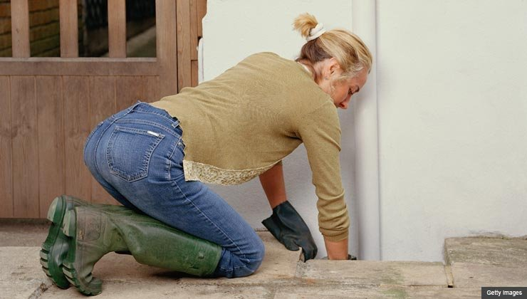 Mature woman kneeling on stone paving, cleaning drain