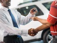 Vendedor dando las llaves de un coche nuevo a un hombre - Cómo comprar un coche con el precio más bajo posible