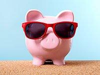 Una alcancía en forma de cerdo en una playa con gafas de sol - Ahorre en utilidades esta primavera