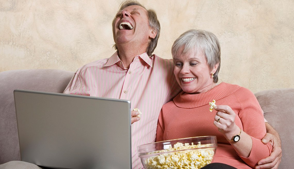 Pareja viendo la televisión en un computador - Gana dinero desde casa.