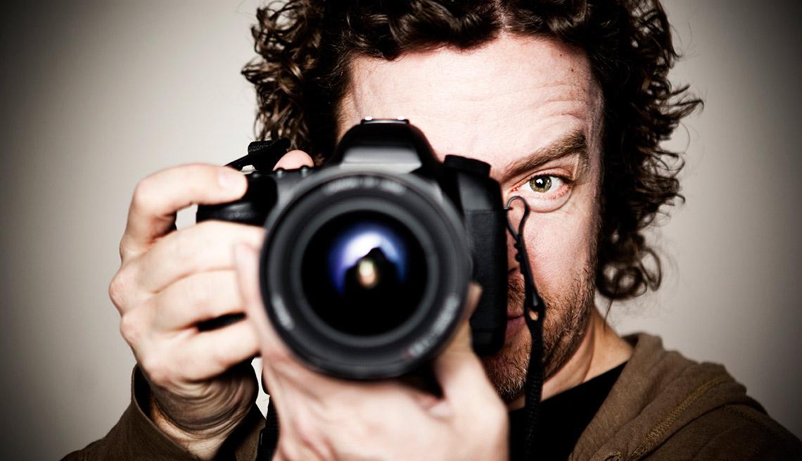 Hombre tomando una foto con una cámara profesional - Gana dinero desde casa