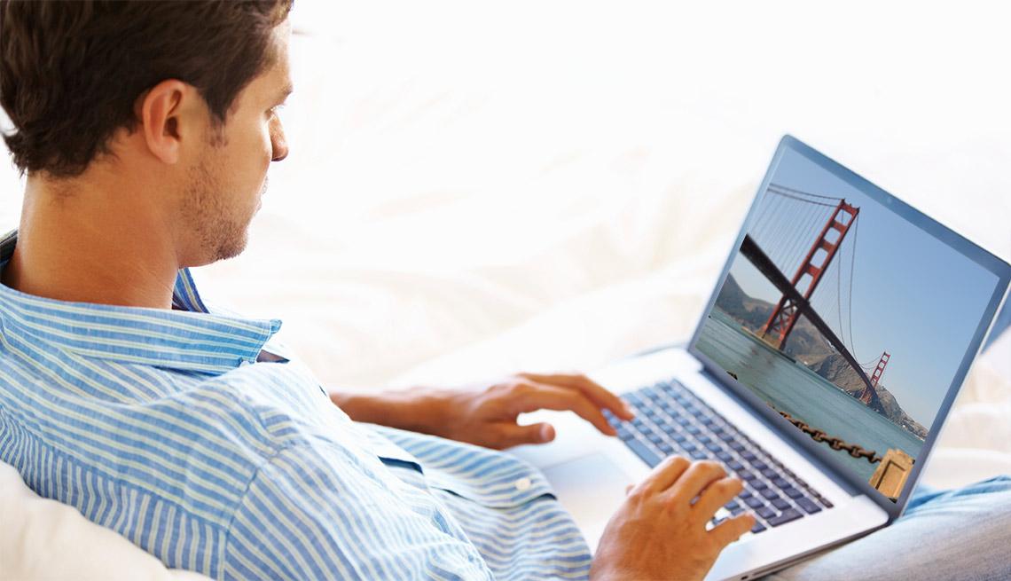 Hombre sentado con un computador portátil en las piernas - Gana dinero desde casa.