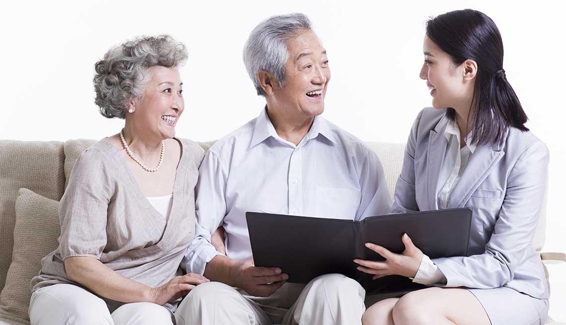 Pareja conversando con un vendedor de seguros - Formas de ahorrar en seguros