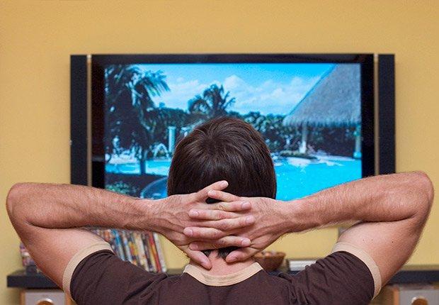 Hombre con las manos sobre la cabeza y viendo la televisión - Gana dinero desde casa.