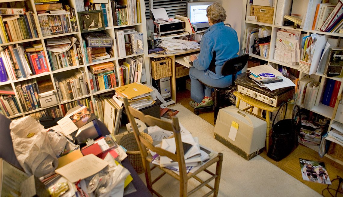 Cuarto con estantes de libros, sillas, cajas y una mujer frente a un computador - Formas de reducir tu espacio