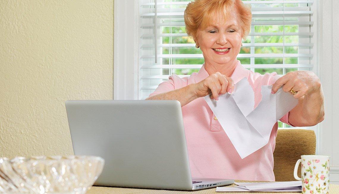 Mujer mayor rasgando papel frente a una computadora personal - Formas de reducir tu espacio