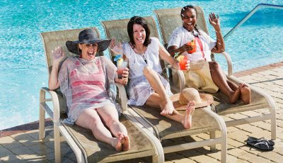 Women having drinks by swimming pool, Things That Are Cheaper in Retirement