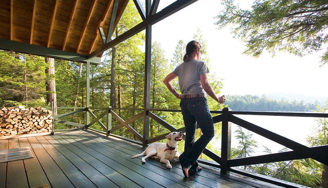 Mujer en una casa de campo con un perro al lado - Cosas que deberías rentar y no comprar