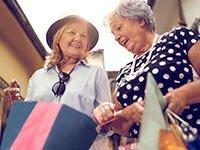 Dos mujeres con bolsas de compras en un centro comercial - Empezar a gastar y dejar de ahorrar en la jubilación