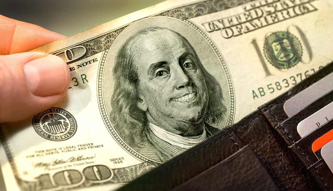 Billete de 100 dólares que una mano saca de una billetera - Quiz del coeficiente intelectual financiero