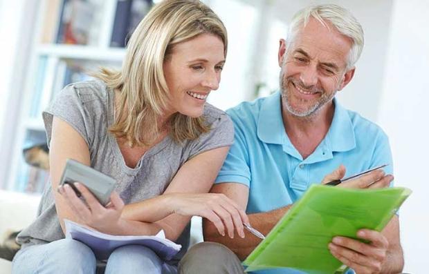 Mujer y hombre sentados en un sofá viendo unos papeles - Maneja tus finanzas como un director ejecutivo.