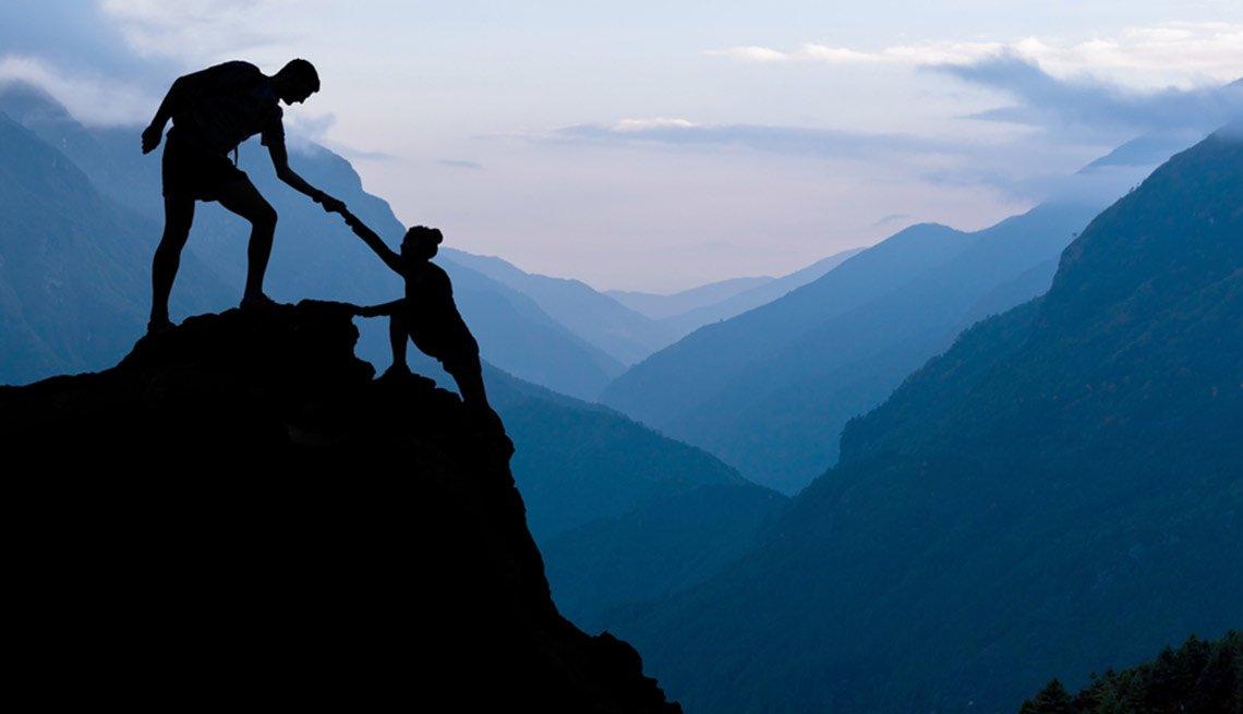 Hombre dándole la mano a una mujer que llega a la cima de una montaña - Becas universitarias inusuales